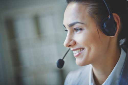 an image of a woman using a telephone headset while she happily talks with customers