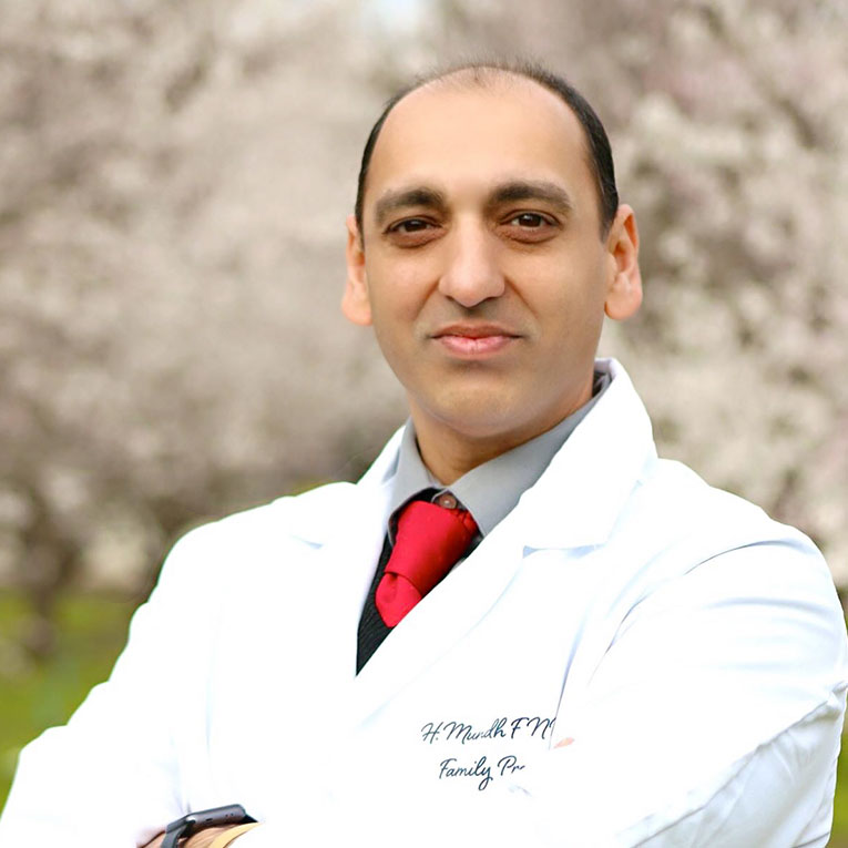 A photo of Hardeep Mundh in his white lab coat, standing in a grove of trees with white flower blossoms on the branches